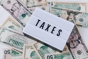 Scattered five, ten and fifty dollar bills with a sign saying Taxes on top.